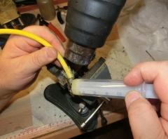 Nun wird das Kabel wasserdicht gemacht. Dazu wird tröpfchenweise die Füllmasse in den Kontaktkörper eingetropft und mit einem Miniaturschraubenzieher oder Pinzette verteilt. Eine weitere Person macht mit dem Heißbläser, nur für kurze Zeit, die Füllmasse flüssiger, damit sie im Kontaktkörper besser verteilt wird.